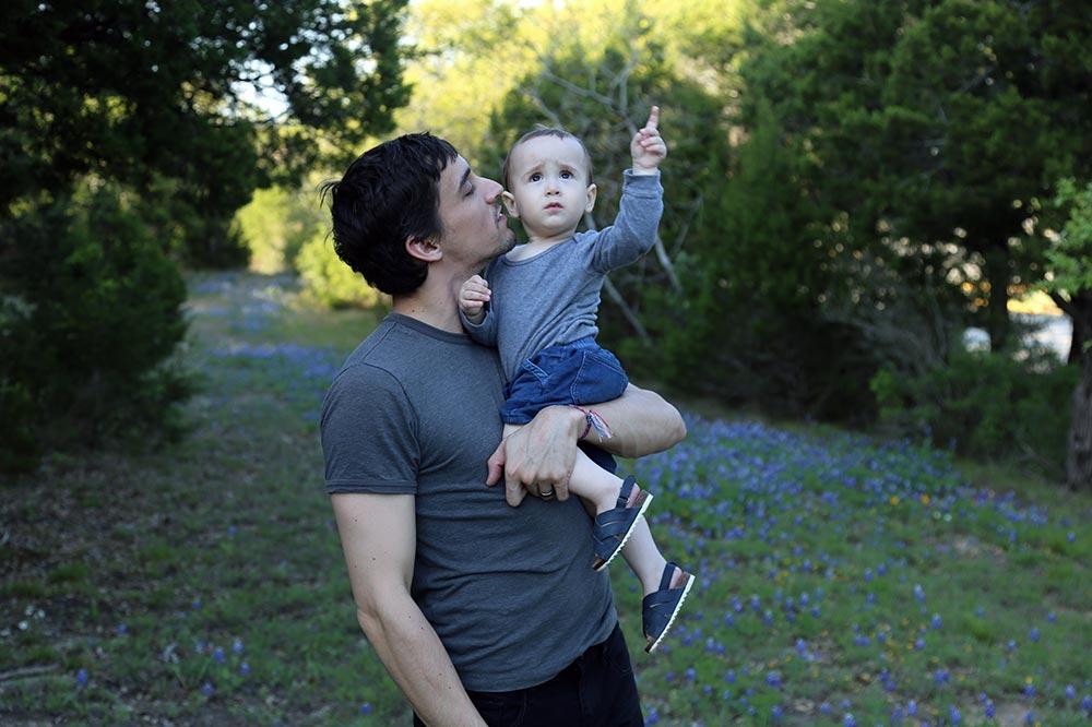 Tyler Garrett holding Andoni Garrett outside pointing into the sky