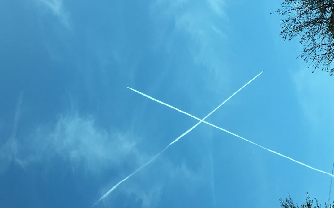 Two planes passing by leaving an X in the blue sky. By Tyler Garrett